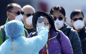 An official in protective suits ensures the temperature of the foreign passengers disembarked from the quarantined Diamond Princess cruise ship before boarding to buses at a port in Yokohama, near Tokyo, Friday, Feb. 21, 2020. Passengers tested negative for COVID-19 started disembarking since Wednesday. (AP Photo/Eugene Hoshiko)